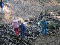 Kinder bauen sich eine Brücke über den Bach.