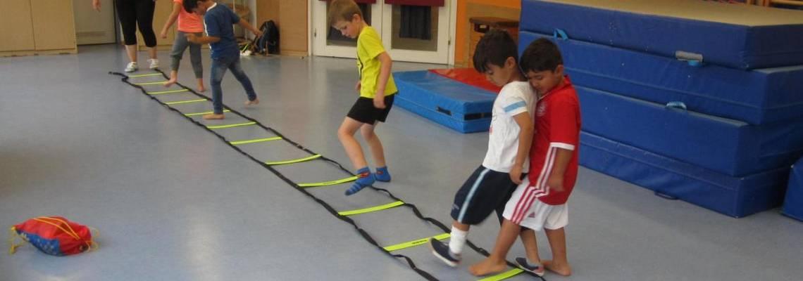 Kinder balancieren auf einer Liegeleiter.