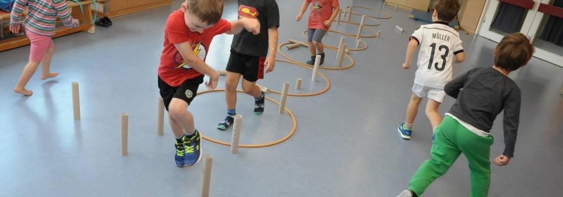 In einer Bewegungsstunden laufen die Kinder einen Parcour mit Hozreifen und Papprollen.
