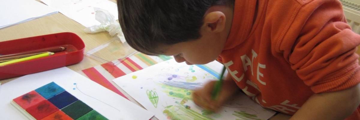 Ein Junge mal mit Stiften und Fingerabdruck ein Bild.