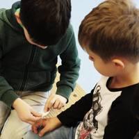 Die Kinder üben ein Pflaster auf eine Wunde zu kleben.