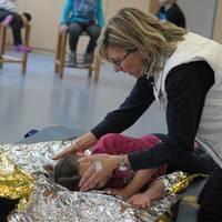 Die Übungsleiterin hilft den Kindern bei der stabilen Seitenlage