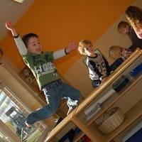 Kind springt vom Regal auf eine Matte