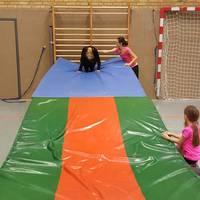 Kinder rollen sich mit einer Vorwärtsrolle an einem Mattenberg runter.