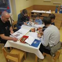 Eltern arbeiten gemeinsam mit Ihren Kindern am Portfolio.