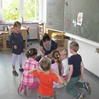 Kinder sitzen gemeinsam mit Lehrerin im Sitzkreis.