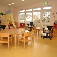 Der Gruppenraum der Blauen Gruppe wird mit Stühlen, Tischen und Spielbreichen gezeigt.
