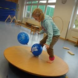 Kind balanciert auf einer Holzscheibe