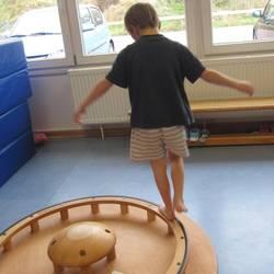 Ein Kind balanciert auf einem Kreisel vom Hengstenberg- Bewegungsmaterial.