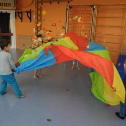 Kinder turnen mit dem Schwungtuch und Naturmaterial- Herbstblätter.