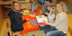 Eltern arbeiten gemeinsam mit Ihren Kindern am Portfolio