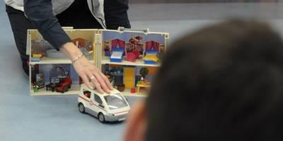 Übungsleiterin zeigt mit Playmobil den Rettungsweg.