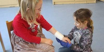 Kinder legen einen Verband an