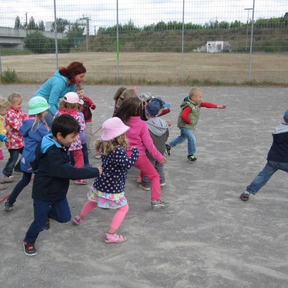 Kinder führen Bewegungsspiele auf dem Bolzplatz durch.