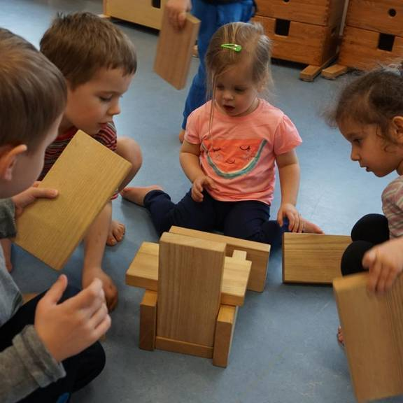 Kinder spielen mit dem Hengstenberg- Bewegungsmaterial aus Holz.
