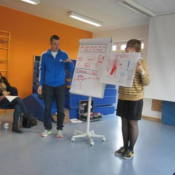 Eine päd. Fachkraft steht mit der Referentin an einer Flipchart und sie bearbeiten das Thema Werte.