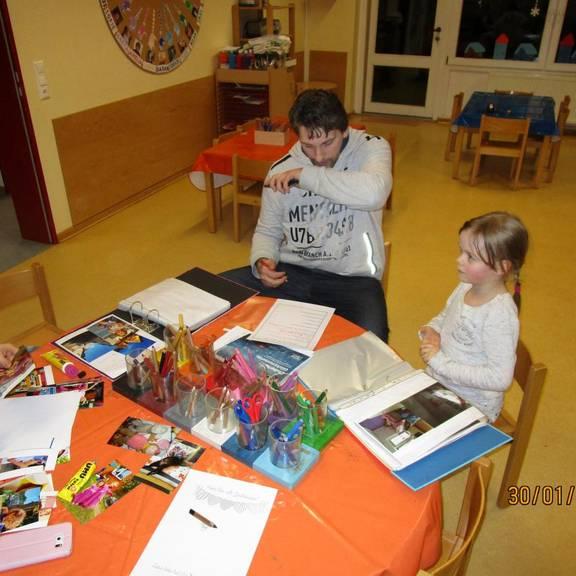 Ein Papa arbeitet zusammen mit seiner Tochter am Portfolioblatt.