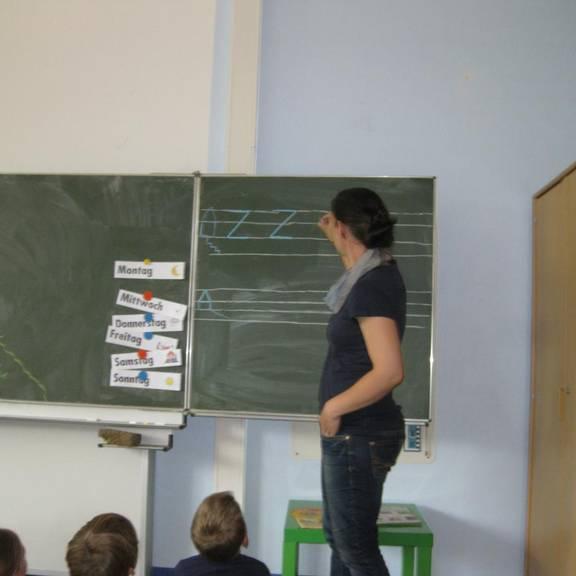 Lehrerin erklärt etwas an der Tafel