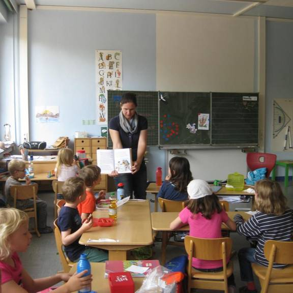 Lehrerin zeigt den Kindern eine Buchseite.
