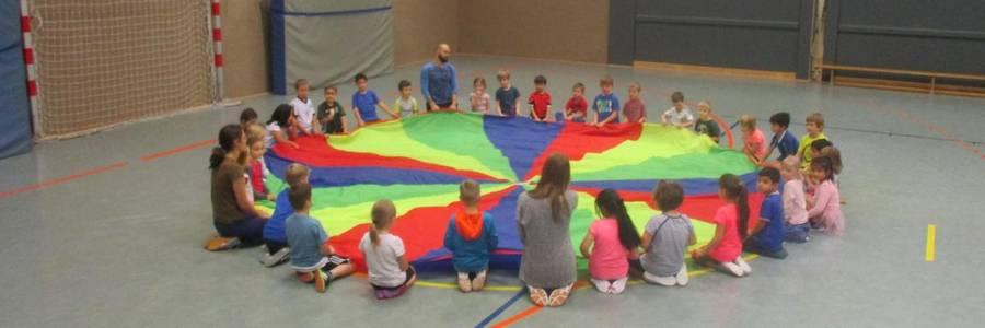 Kinder halten ein Schwungtuch im Kreis.