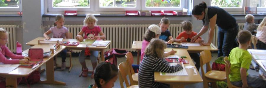Kinder sitzen an Schultischen und erarbeiten sich etwas.